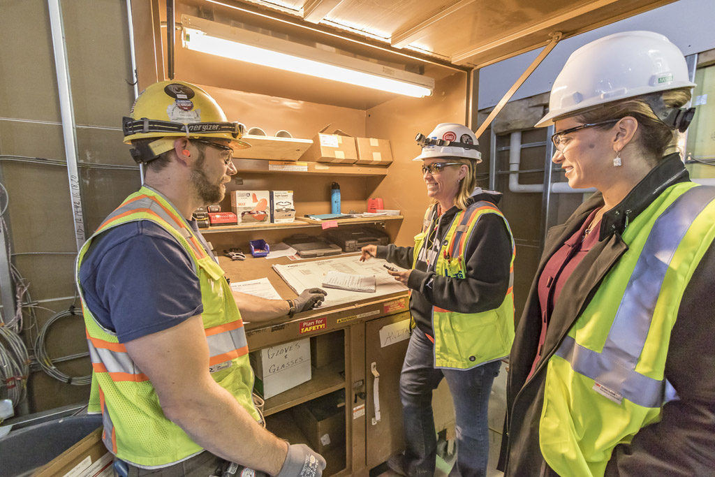 Kara Fox-LaRose (right) consults with Anita Foreman, the electrical foreman for OEG of Portland, and member of the Cowlitz Indian Tribe (center) and Mark Gable, journeyman wireman for OEG (left) at the construction site of the ilani casino-resort on Wed., Oct. 5. Photo by Mike Schultz