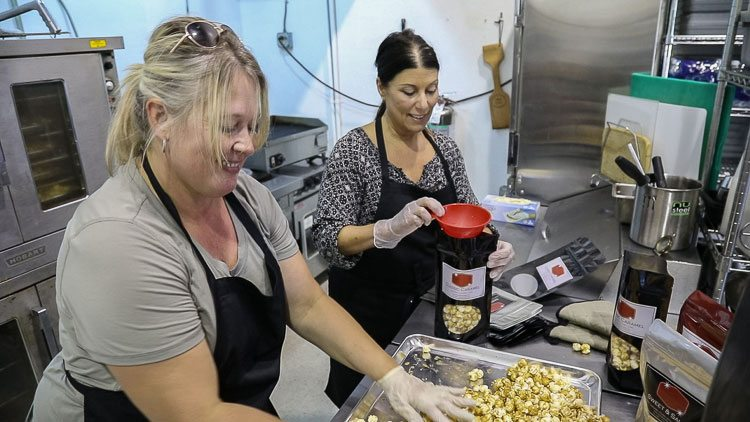 Kristi Kotrous (left) and Chris Fried (right) work together to make caramel corn, one of three products they produce for their business -- Serendipity Doo Dah. Photo by Mike Schultz