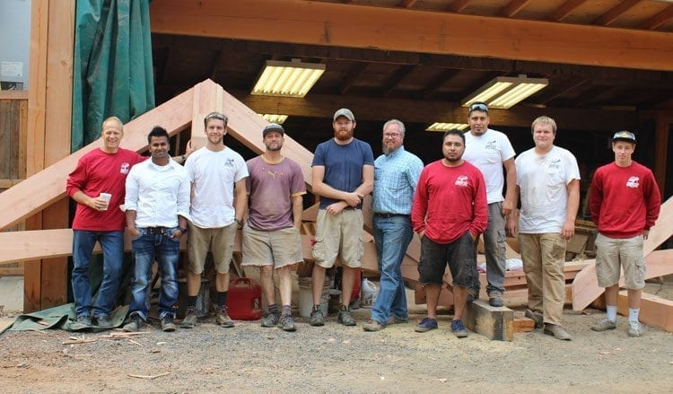 Bert Sarkinnen (left) and Matthew Duvall (second from left) stand with the Arrow Timber Framing team in front of a truss at the company's Battle Ground shop. Photo by Alex Peru