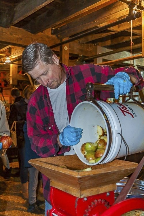 After being chopped, apple pieces were placed into a grinding machine driven by belts and pulleys powered by water from Cedar Creek, as demonstrated by Ken Clark. Photo by Mike Schultz