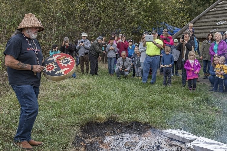 Chinook Tribal Vice Chairman, Sam Robinson, plays a drum during the blessing of food and friendship before the traditional salmon bake at the Cathlapotle Plankhouse, at the Carty Unit of the Ridgefield National Wildlife Refuge during 2016 BirdFest. Photo by Mike Schultz.