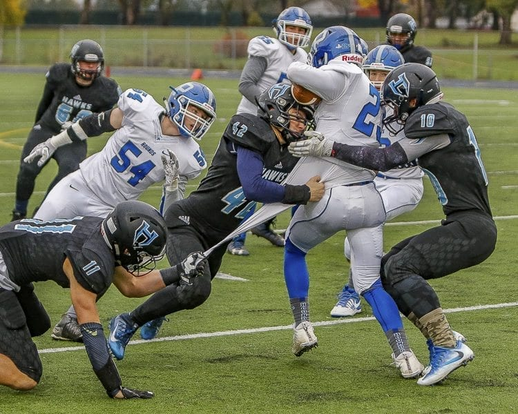 A trio of Hockinson defenders — Sawyer Racanelli (11), Jonathon Domingos (42) and Kyle Brabec (10) — stop Pullman running back Dylan Hodge (23) during the Hawks' 53-18 victory in a first round state playoff game played Friday at District Stadium in Battle Ground. Photo by Mike Schultz