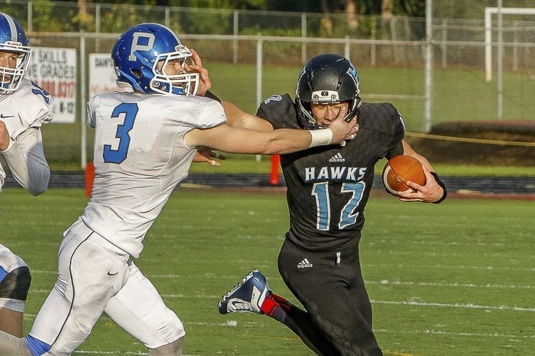 Hockinson quarterback Canon Racanelli (12) uses a stiff arm to fend off a Pullman defender during a second quarter run in the Hawks' state playoff game Friday at District Stadium in Battle Ground. Photo by Mike Schultz