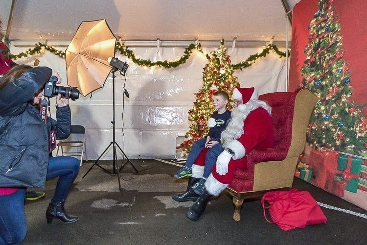 Many families lined up outside of a tent to have their childrens' pictures taken with Santa Claus during Camas' Hometown Holidays on Friday. Camas resident Lisa Kuhlman worked as the photographer, and Rick Knapp of Camas appeared as Santa Claus. Here, Harley Kays smiles for the camera and tells Santa what he wants for Christmas. Photo by Mike Schutlz