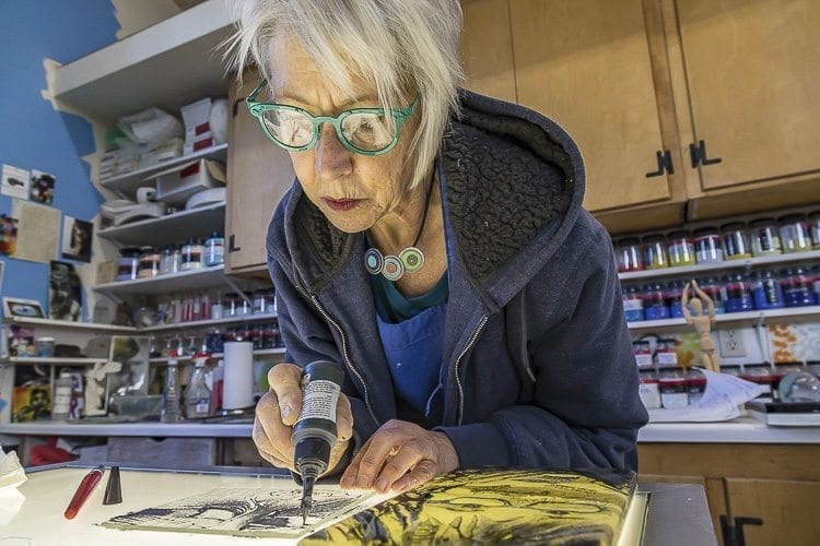 Sharon Agnor works with cast glass as well as metal. She can create designs on panes of glass by spreading tiny colored powdered glass on the pane, similar to painting. The powder is then fired in a kiln to create the artwork. Photo by Mike Schultz