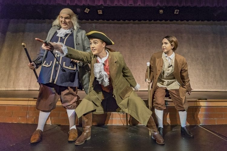 """Natalie Williams as Richard Henry Lee (center) makes another point in front of Jordyn Fields' Benjamin Franklin and Rowan Segura's John Adams during Heritage's production of """"1776,"""" now performing at the high school. Photo by Mike Schultz"""
