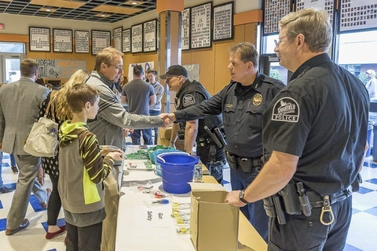 Todd and Noah Swenson meet with Ridgefield police officer Craig Wattson, Chief John Brooks, and Lt. Roy Rhine at Wednesday's Ridgefield School Safety Open House. Photo by Mike Schultz.