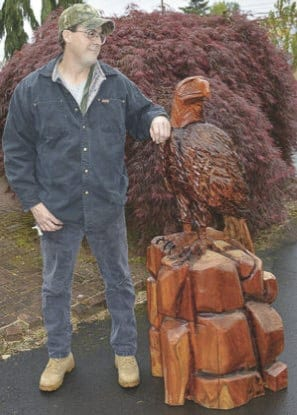 Area artist Carl Fender is shown here with a previous carving he donated to the North County Community Food Bank. Photo courtesy of North County Community Food Bank