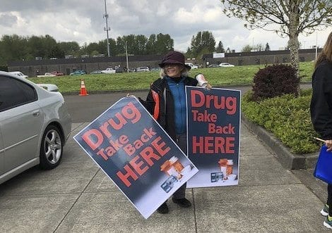 Kris Soske holds signs at the Battle Ground Police Department for the Drug Take Back event. Photo provided by Educational Service District 112