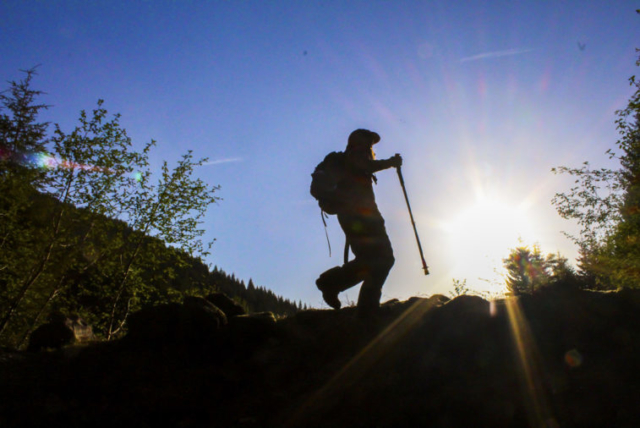The sun shines as a climber walks across a small ridge at Mount St. Helens. Photo by Eric Schwartz