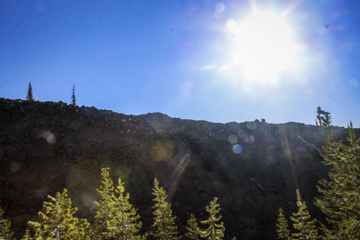The sun shines behind a boulder field at Mount St. Helens. Photo by Eric Schwartz