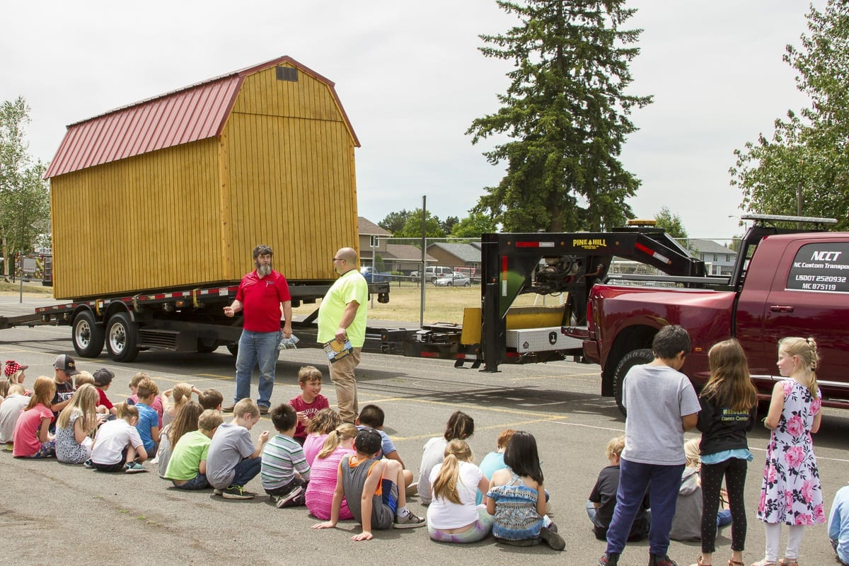 Nick Cutler demonstrated how his company uses special flatbed trailers to deliver large sheds to homes and businesses. Photo courtesy of Woodland School District