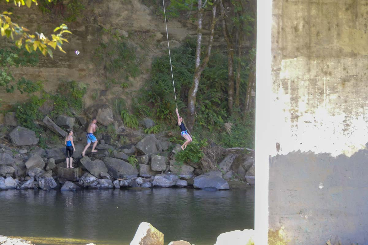 Children enjoy a rope swing on the north end of the Daybreak Road Bridge, and a splash in the East Fork Lewis River. Photo by Chris Brown