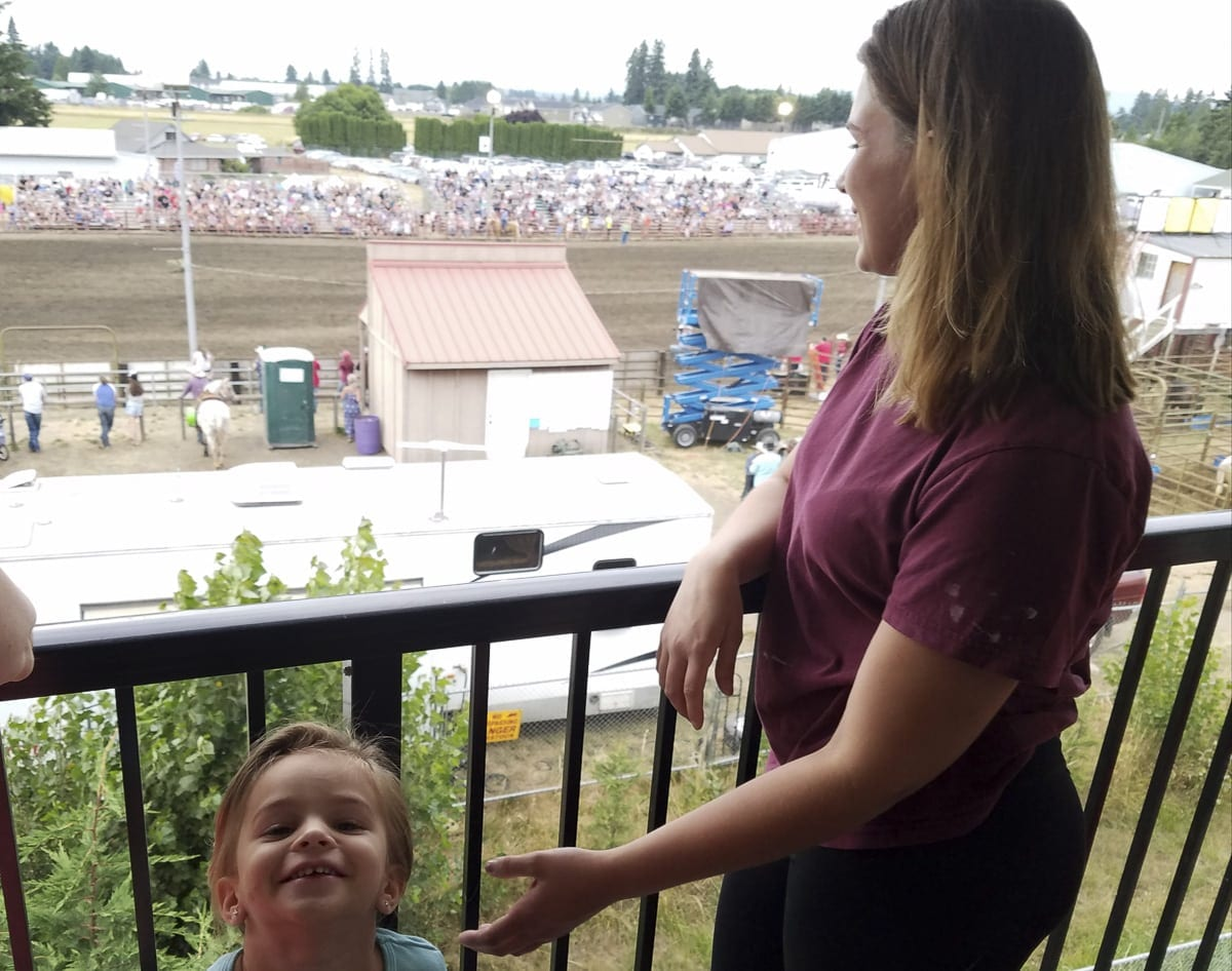 Jessica Malik and 4-year-old Myah enjoy the view from their third-level balcony from their apartment complex next to the Clark County Saddle Club. This likely will be the last rodeo at this location, though. The club is in negotiations to sell the land. Photo by Paul Valencia