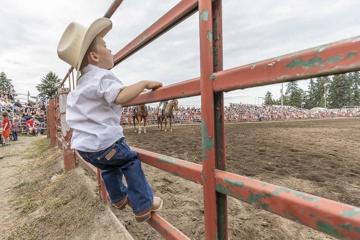 James Garrison, a 3-year-old from California, takes a step to get a closer look at the action at the Vancouver Rodeo. Photo by Mike Schultz