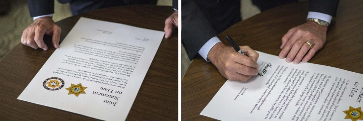 """Sheriff Chuck Atkins signs the """"Joint Statement on Hate"""" in the graphic design office at the Public Service Center in Vancouver. Photo by Jacob Granneman"""