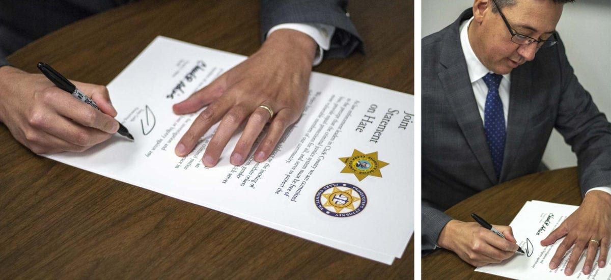 """Clark County Prosecuting Attorney Tony Golik signs the """"Joint Statement on Hate,"""" moments after Sheriff Atkins on Wednesday. Photo by Jacob Granneman"""