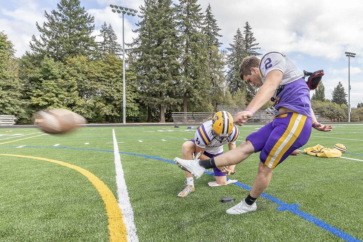 Columbia River's Matt Asplund holds for kicker Tristan Hoyer at a recent Chieftains' practice. Photo by Mike Schultz