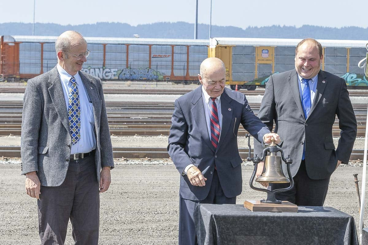 Port of Vancouver Commissioner Jerry Oliver (center) rings a ceremonial bell to mark the opening of the West Vancouver Freight Access project as Commissioners Don Orange (left) and Eric LaBrant watch. Photo by Mike Schultz