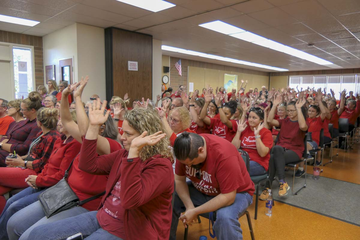 Battle Ground teachers wave their hands in a show of support during Monday's school board meeting. Photo by Chris Brown