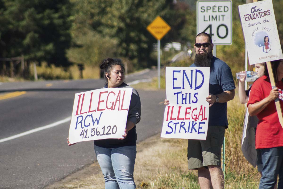 Stephen and Victoria Culley hold signs along SR-503 in Battle Ground protesting the striking teachers. Photo by Jacob Granneman