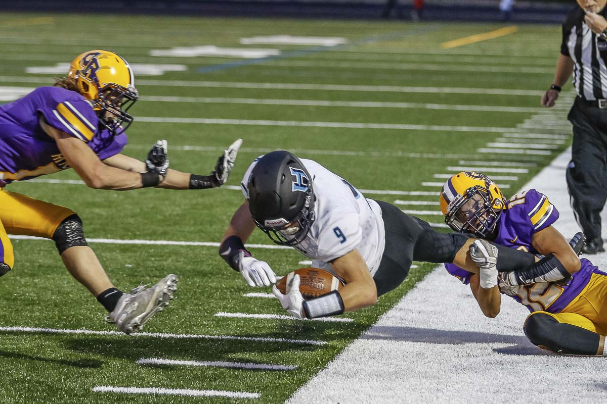Hockinson receiver Peyton Brammer (9) stretches for every inch while Columbia River defender Benjamin Bisquera (12) makes the leg tackle. Photo by Mike Schultz