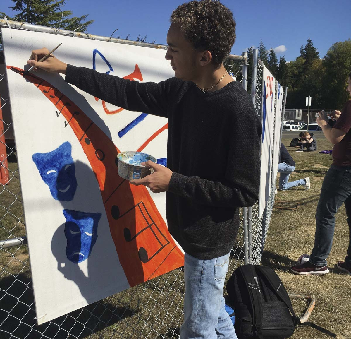 Kyshaun Summers, a Ridgefield High School senior, creates a drama and music art panel for the construction site fence line at his school. Photo courtesy of Ridgefield School District