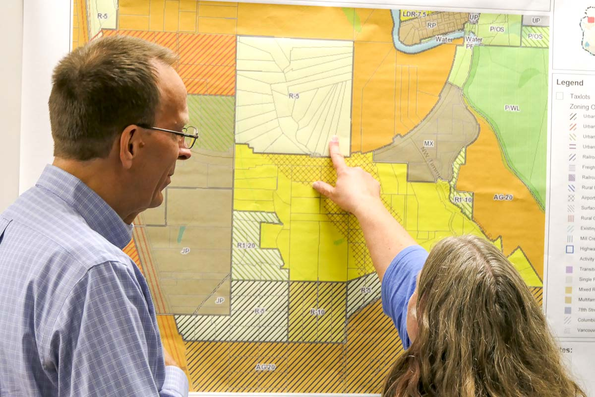 Paul Lewis, a consultant for the city of La Center, explains their Latecomer Agreement with the Cowlitz Tribe to a property owner at an open house. Photo by Chris Brown