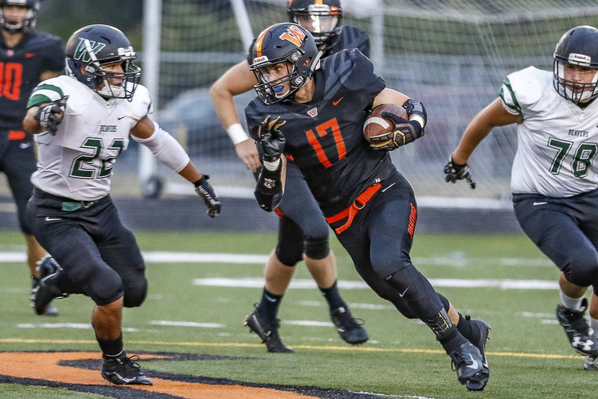 Washougal's Brevan Bea (17) rushes with the football in Friday's action against Woodland at Washougal High School. In pursuit are Woodland defenders Elijua Schultz (22) and John Arocan (78). Photo by Mike Schultz