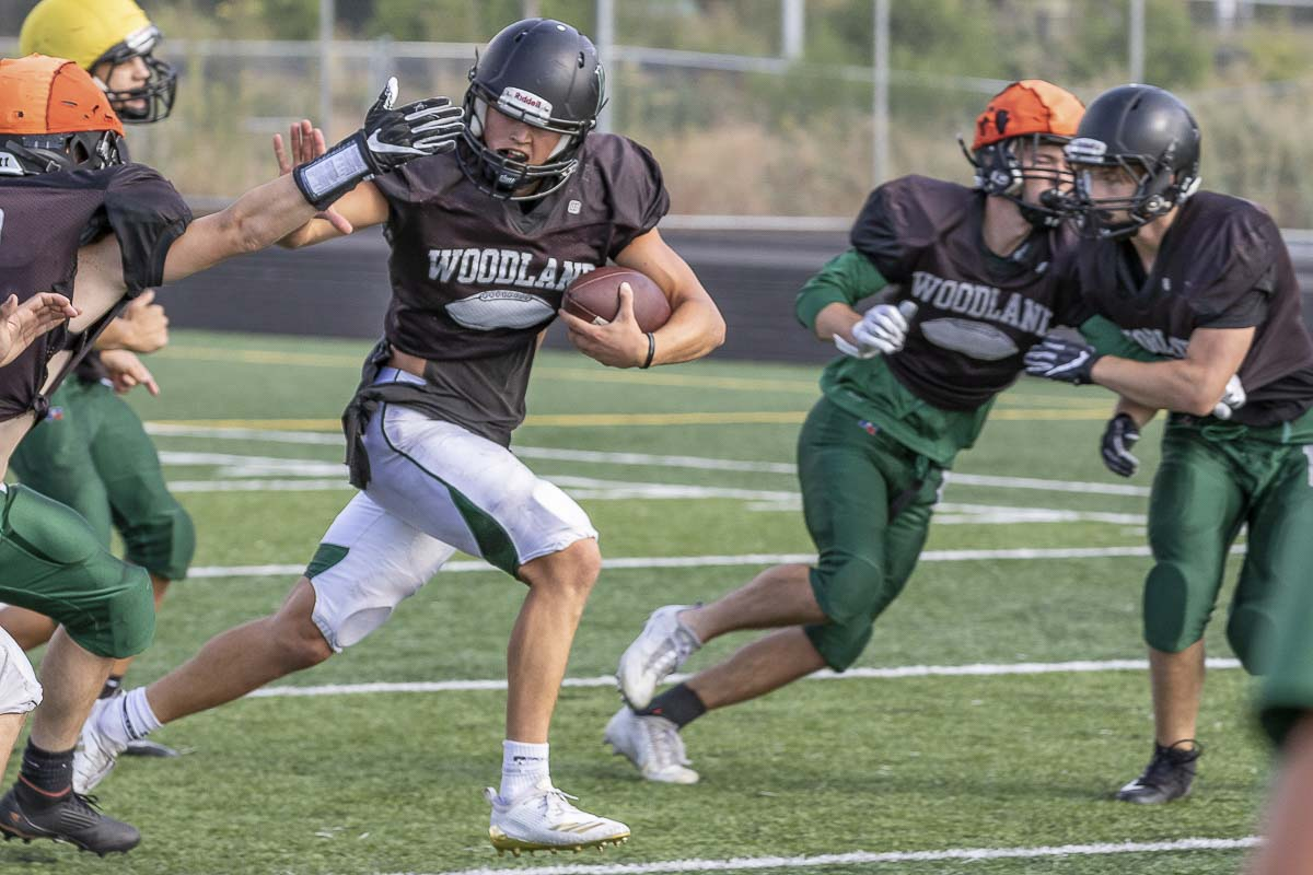 Tyler Flanagan plays like he practices. Shown here in practice breaking free, he did that a lot in Week 1, rushing for four touchdowns and passing for two TDs in Woodland's victory. Photo by Mike Schultz