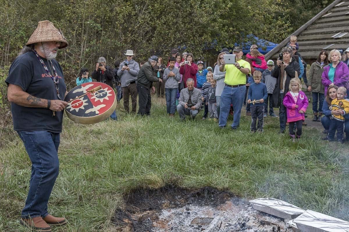 Spectators watch as Chinook Tribal Vice Chairman, Sam Robinson, plays the drum prior to the traditional salmon bake at the 2017 Birdfest. Photo by Mike Schultz