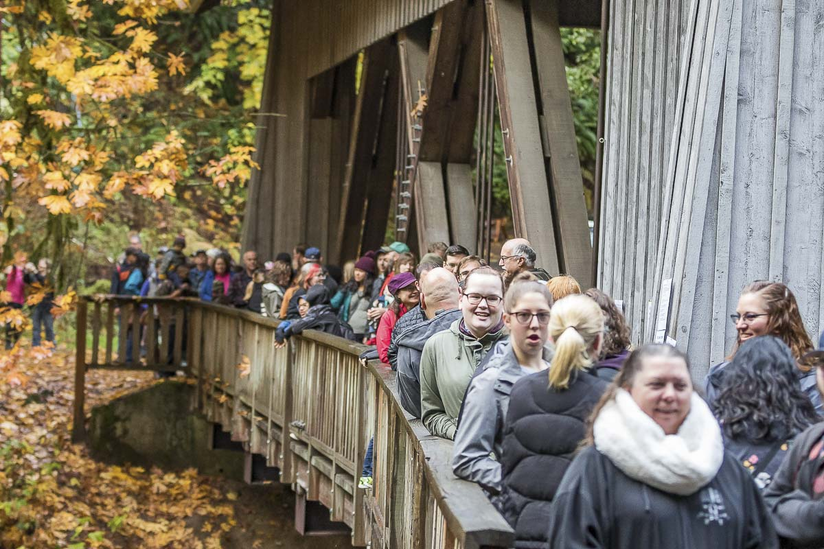 People lined up across the covered bridge leading to the Cedar Creek Grist Mill for Apple Cider Pressing Day. Photo by Mike Schultz