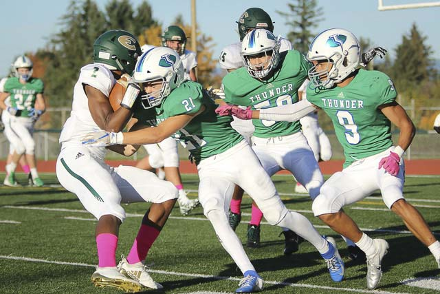 Jordan Cook (21) and Phillip Earnhardt (9) of Mountain View close in on Zyrell Griffin (2) of Evergreen in Thursday's Class 3A Greater St. Helens League football game. Mountain View won 55-14. Photo courtesy of jkgulli photography
