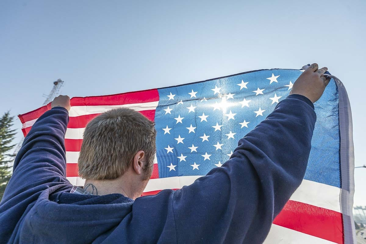 A member of Patriot Prayer holds up an American flag during a rally in Vancouver on Oct. 22. Photo by Mike Schultz