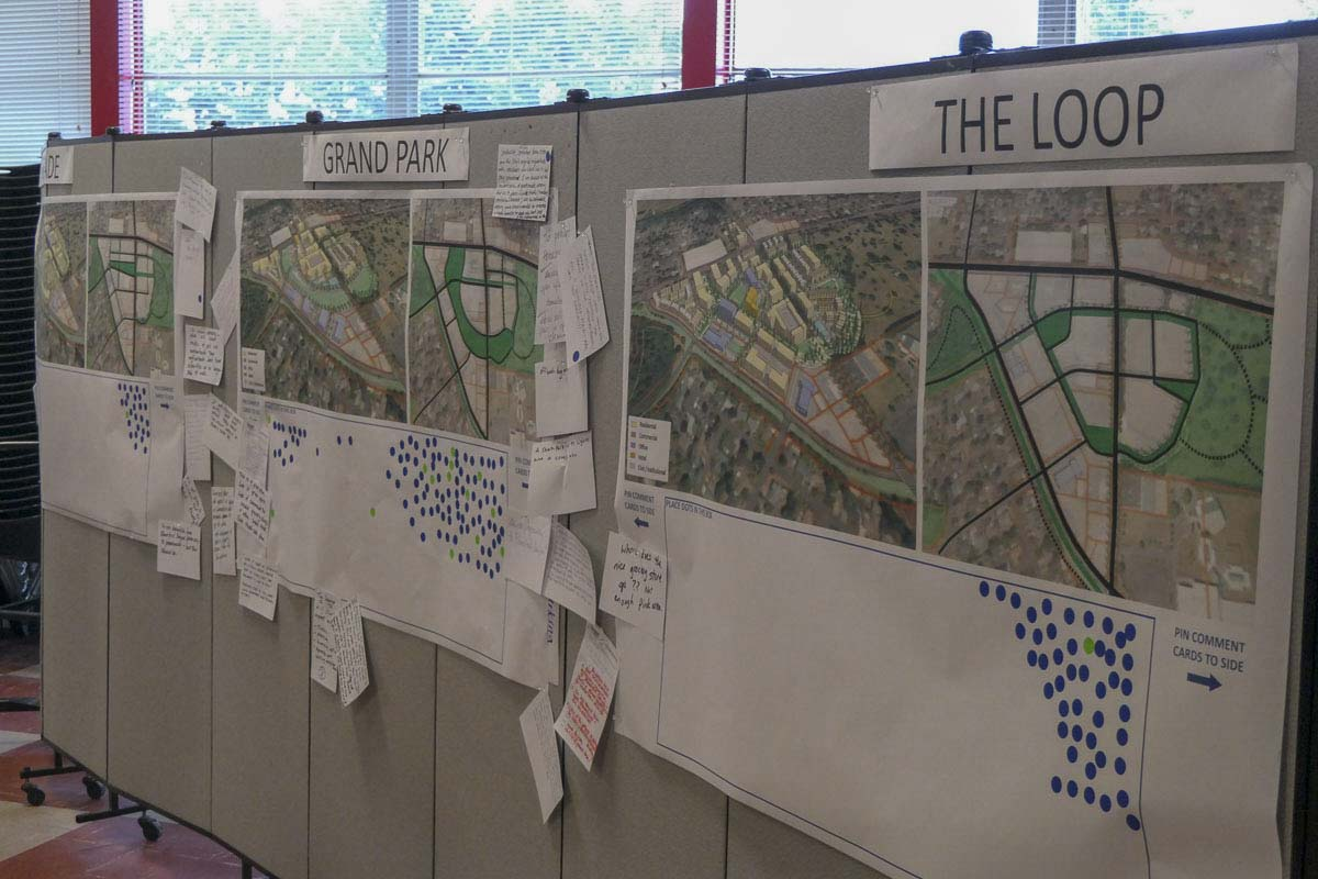 Citizens leave blue dots on the concepts they prefer at an open house for the Tower Mall site redevelopment plan. Photo by Chris Brown
