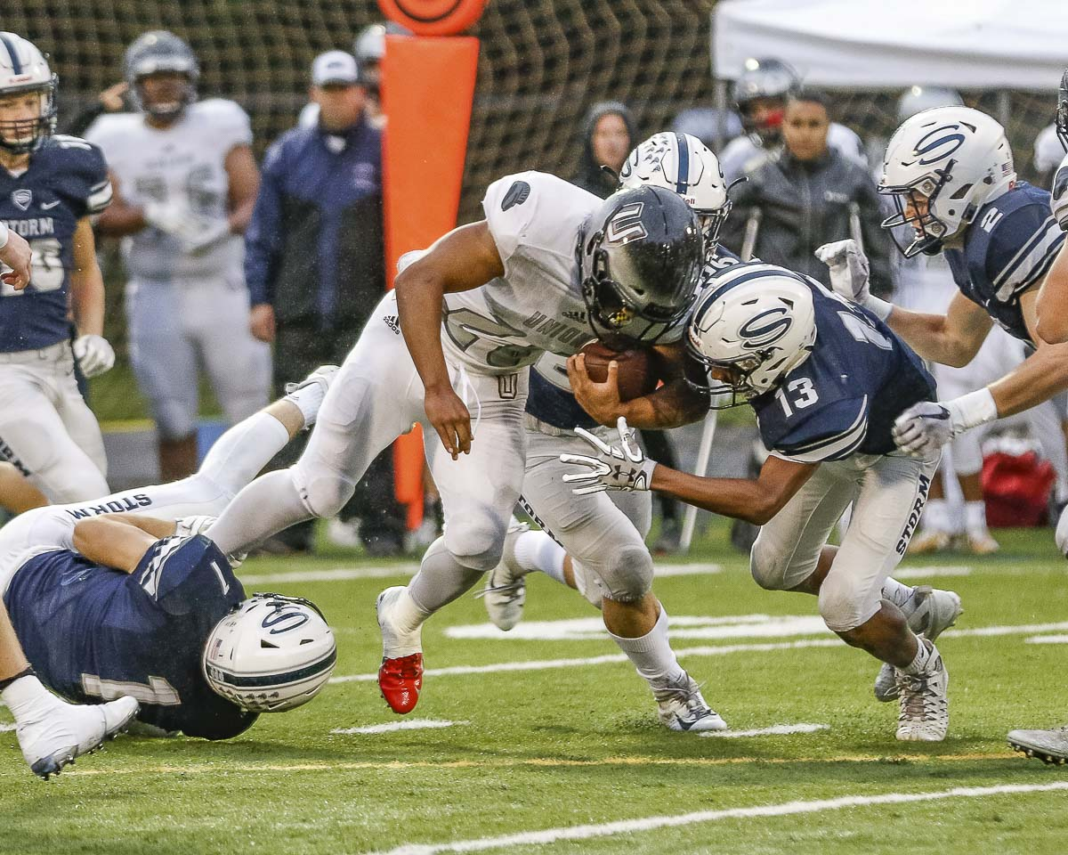 Union running back Joseph Siofele (26) struggles for yardage while Skyview's Xavier Owens (13) moves in for the tackle during the Titans' 21-15 victory over the Storm Friday at Kiggins Bowl. Photo by Mike Schultz