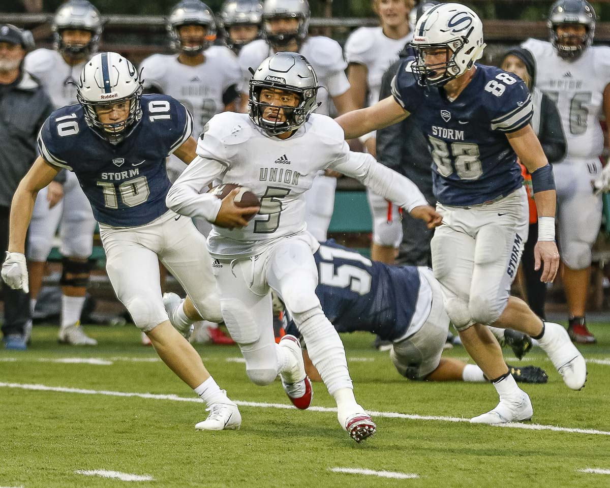 Union quarterback Lincoln Victor (5) scrambles for yardage Friday at Kiggins Bowl. In pursuit are Skyview defenders Saunders Buck (10) and Micah Baylous (88). Photo by Mike Schultz