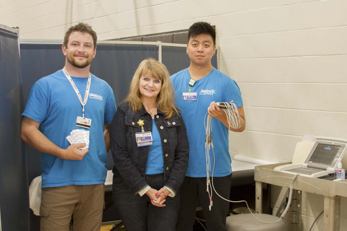 Lydia Hibsch, Business & Community Development manager, demonstrates the electrocardiogram (EKG) scanner with two of her colleagues. Photo courtesy of Woodland School District