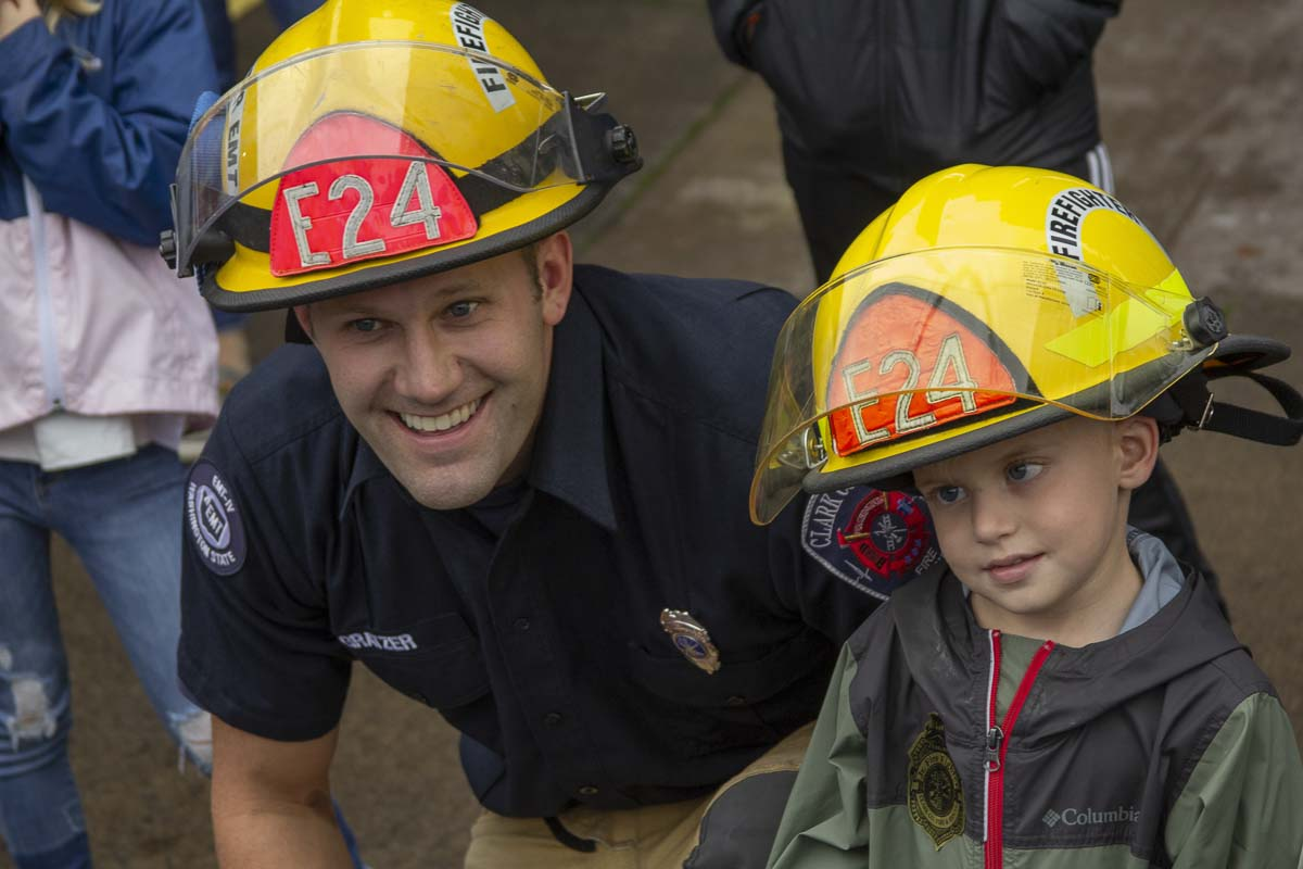 Firefighter Colby Gratzer poses with Wyatt Draper after presenting him with his very own firefighter helmet with his name emblazoned across the back. Photo by Jacob Granneman
