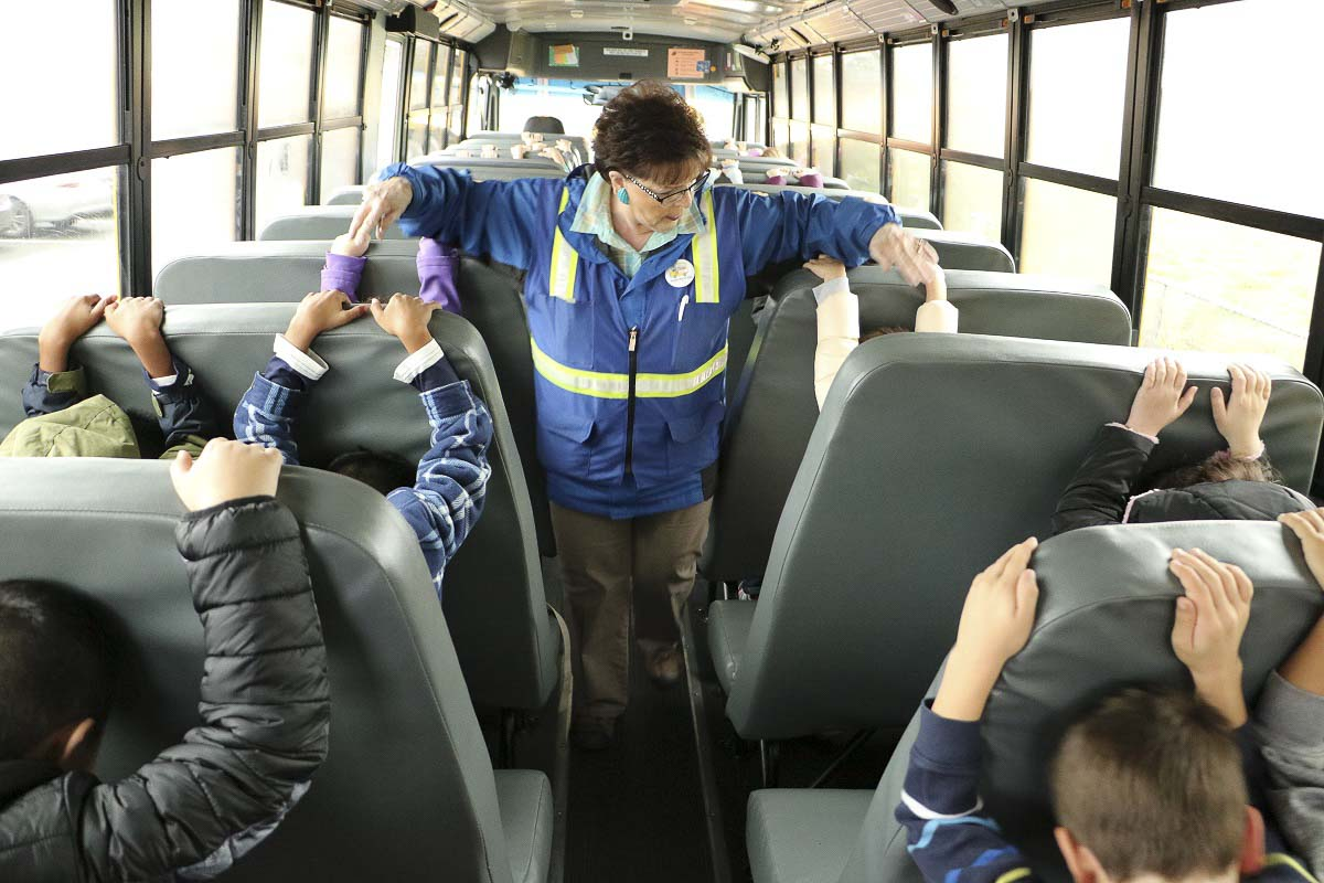 Helen Peterson checks on students who are practicing earthquake safety. Photo courtesy of Battle Ground Public Schools