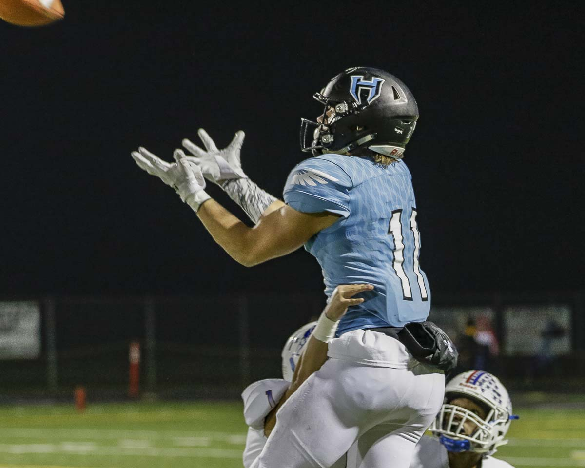 Hockinson receiver Sawyer Racanelli (11) soars high in the air to gather in a pass during the Hawks' win over Washington in the first round of the Class 2A state high school football playoffs at District Stadium in Battle Ground. Photo by Mike Schultz