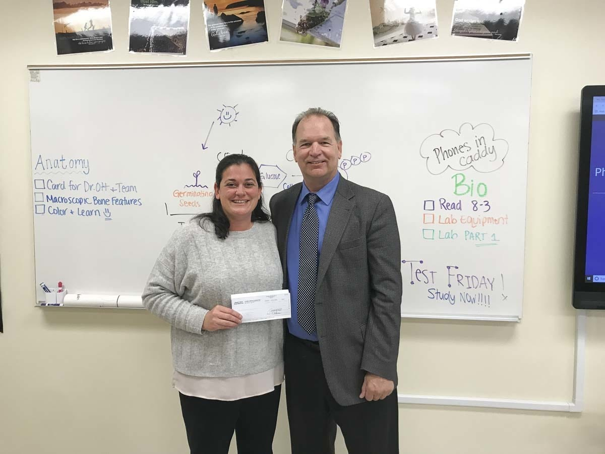 King's Way Christian School Biology teacher Juli Bristowe (left) accepts a check for $3,905 from Toshiba America Foundation representative Bruce Engberg (right). The STEM Grant will support the implementation of new biotechnology lab equipment for high school students and improve inquiry-based science instruction with a continuum of learning experiences. Photo courtesy of King's Way Christian Schools
