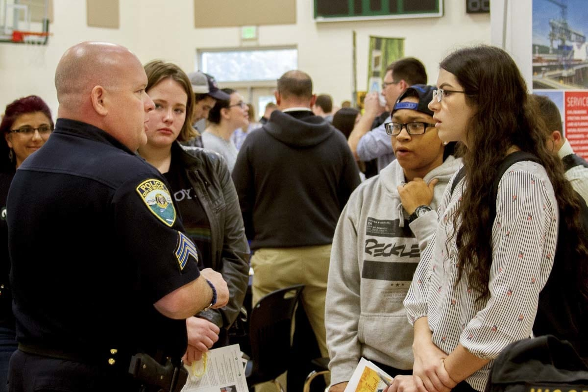 Woodland students Kylie Knitz, Jaelyn Dodds, and Karlee Cresap speak with a Woodland City police officer about his experiences working in law enforcement. Photo courtesy of Woodland Public Schools