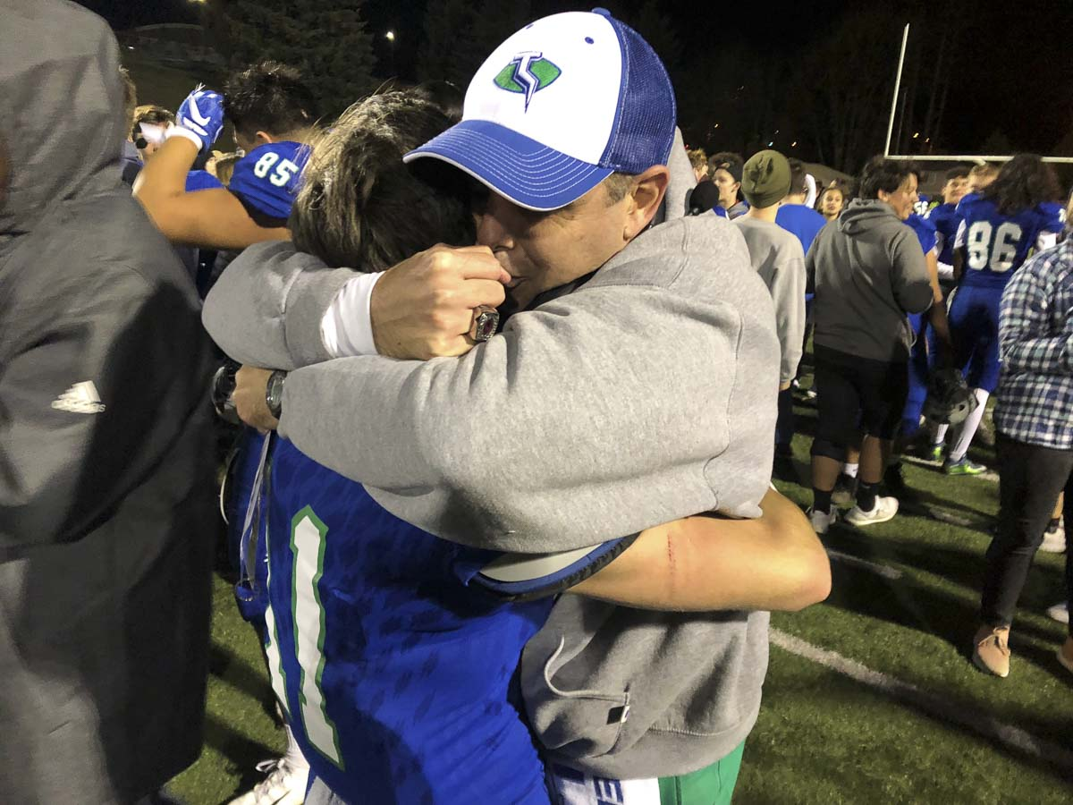 Mountain View coach Adam Mathieson and Thunder quarterback Garrett Moen celebrate Saturday's state playoff win with a hug. Photo by Mike Schultz