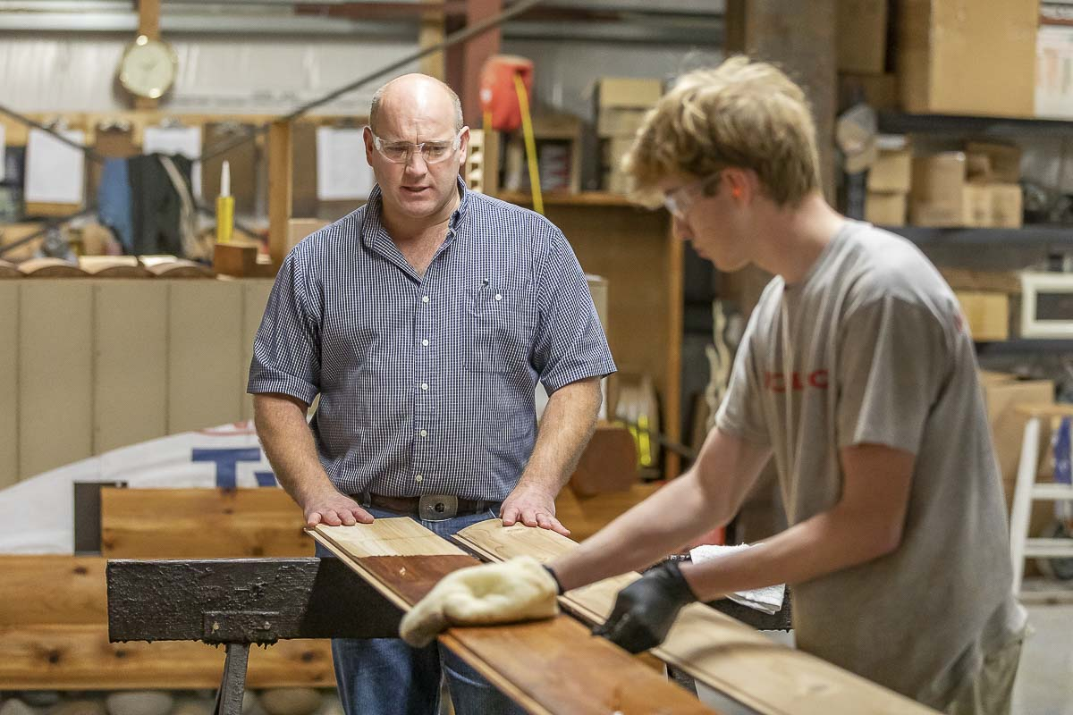 Sean McConeghy, (left), explains the process of staining the select tight-knot Western Red Cedar they use for Modulog Inc.'s log siding, while his son Trevor, (right), stains the wood. Photo by Mike Schultz