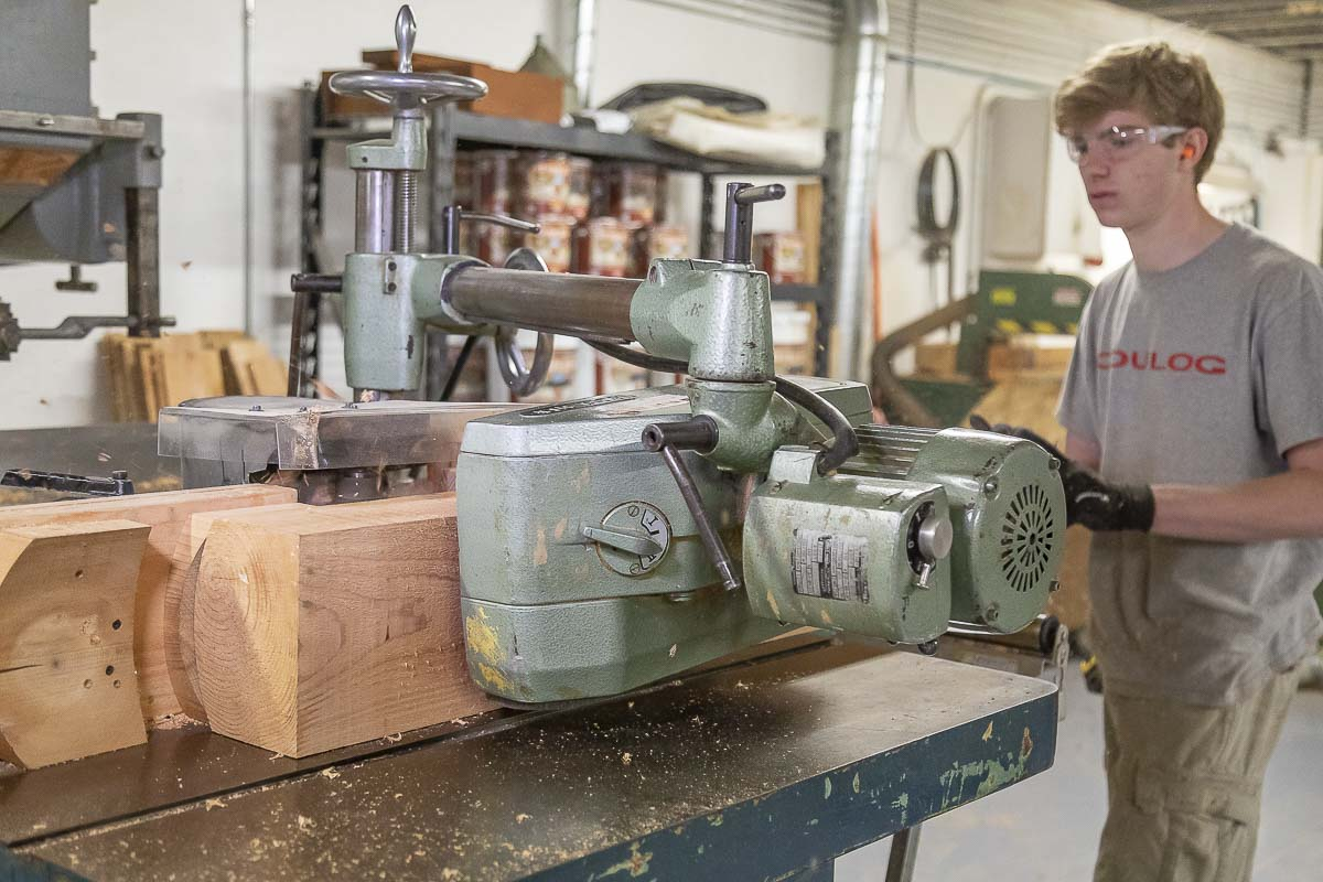 Trevor McConeghy pushes a cedar board through a type of router device that creates the curved surface of the log siding. Photo by Mike Schultz