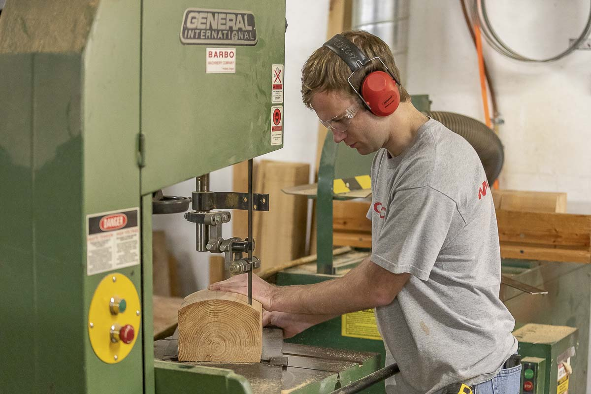 Tyler McConeghy, Sean's oldest son, cuts out a cup-shaped space using a band saw. This allows for the faux log ends to bind tightly together when glued. Photo by Mike Schultz