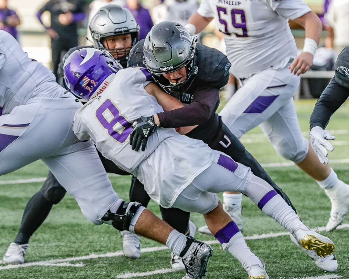 Hockinson linebacker Jack Eggleston (15) puts a hit on Puyallup running back Kyle Cramer (8) during the Hawks' semifinal win Saturday at McKenzie Stadium. Photo by Mike Schultz