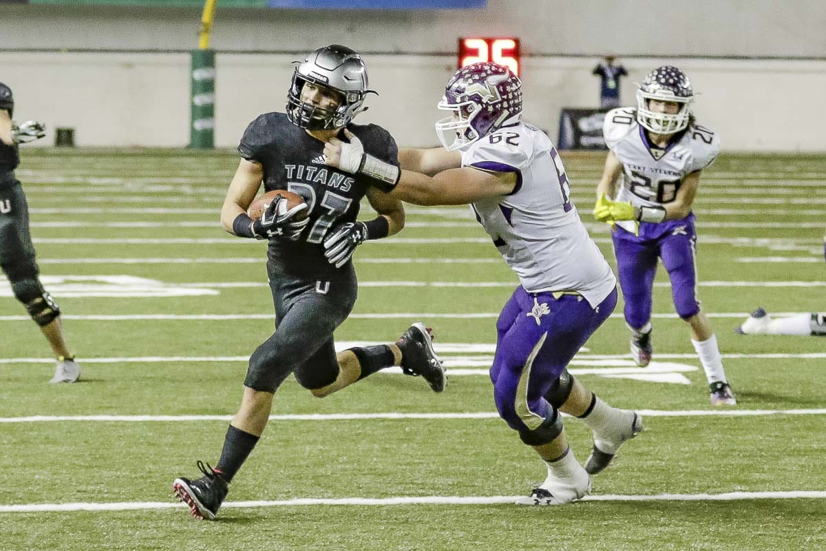 Union defensive back Alex Vallejo (27) returns the football for yardage after a fumble recovery. The Titans' defense shutout Lake Stevens in the second half Saturday and Union cruised to a 52-20 win in the Class 4A state high school football championship game at the Tacoma Dome. Photo by Mike Schultz