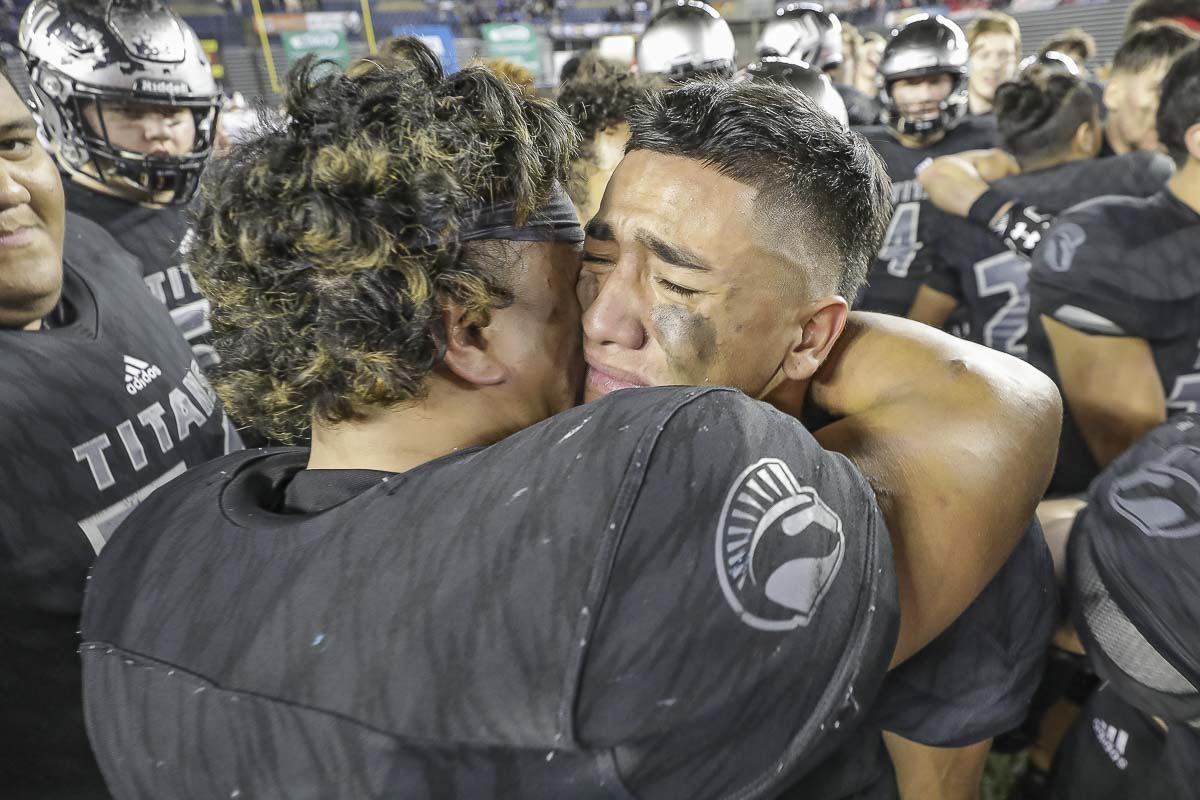 Union standouts Jojo Siofele (left) and Lincoln Victor (right) embrace after leading the Titans to a 52-20 victory over Lake Stevens in the Class 4A state high school football championship game Saturday at the Tacoma Dome. Photo by Mike Schultz